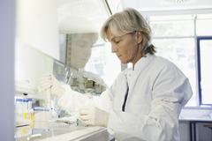 Stock Photo of Germany, Bavaria, Munich, Scientist researching blood in laboratory