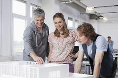 Germany, Bavaria, Munich, Man explaining architectural model to colleagues Stock Photos