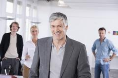 Stock Photo of Germany, Bavaria, Munich, Men and woman in office, smiling, portrait