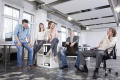 Germany, Bavaria, Munich, Men and women in office, smiling Stock Photos