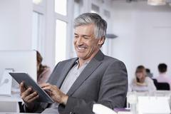 Stock Photo of Germany, Bavaria, Munich, Mature man using digital tablet, colleagues working in