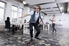 Germany, Bavaria, Munich, Man skate boarding in office while colleagues working - stock photo