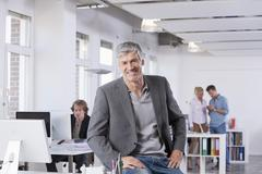 Germany, Bavaria, Munich, Mature man smiling, colleagues in background - stock photo