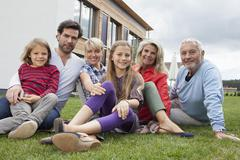 Germany, Bavaria, Nuremberg, Family sitting in front of house, smiling, portrait - stock photo