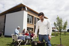 Stock Photo of Germany, Bavaria, Nuremberg, Man cooking barbecue, family sitting in garden