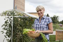 Germany, Bavaria, Nuremberg, Mature woman with vegetables in garden - stock photo