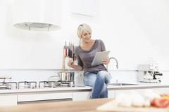Germany, Bavaria, Munich, Woman watching digital tablet and preparing food Stock Photos