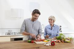 Germany, Bavaria, Munich, Mature couple chopping vegetables in kitchen, smiling - stock photo