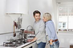 Germany, Bavaria, Munich, Mature couple preparing food in kitchen Stock Photos