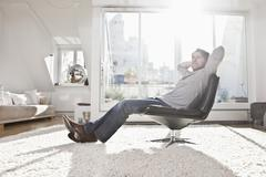 Stock Photo of Germany, Bavaria, Munich, Man sitting on armchair