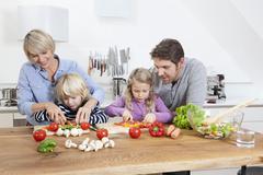 Stock Photo of Germany, Bavaria, Munich, Family preparing food in kitchen