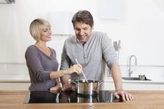 Stock Photo of Germany, Bavaria, Munich, Mature couple cooking food in kitchen, smiling