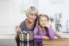 Stock Photo of Germany, Bavaria, Munich, Mother and daughter preparing food, smiling, portrait