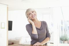 Stock Photo of Germany, Bavaria, Munich, Woman using mobile phone, smiling