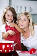 Germany, Mother and daughter eating noodles in kitchen - stock photo