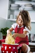 Stock Photo of Germany, Girl playing with spaghetti