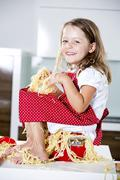 Germany, Girl playing with spaghetti on kitchen worktop - stock photo