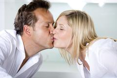 Stock Photo of Germany, Mid adult couple eating noodles and kissing