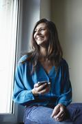 Stock Photo of Germany, Cologne, Mid adult woman at window with cell phone, smiling