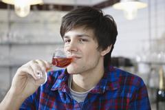 Germany, Cologne, Young man drinking wine, smiling - stock photo