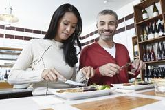 Germany, Cologne, Couple eating food in kitchen, smiling Stock Photos