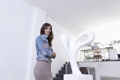 Stock Photo of Germany, Cologne, Mid adult woman standing near sculpture in art gallery,