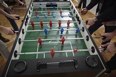 Germany, Cologne, Men and women playing table soccer Stock Photos