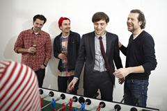 Germany, Cologne, Men and women playing table soccer - stock photo