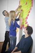 Germany, Cologne, Men and woman sticking paper note on wall - stock photo