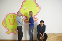 Germany, Cologne, Men and woman with paper note on wall - stock photo