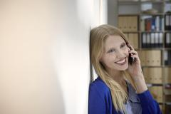 Stock Photo of Germany, Cologne, Young woman on cell phone, smiling