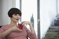 Stock Photo of Germany, Cologne, Young woman sitting with glass of tea in apartment