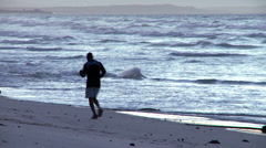 Man jogging on the beach Stock Footage