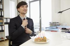 Stock Photo of Germany, Cologne, Mid adult man with birthday cake, smiling