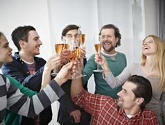 Germany, Cologne, Men and women toasting with champagne in office Stock Photos