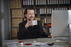 Germany, Cologne, Mature man with coffee cup in office, smiling Stock Photos