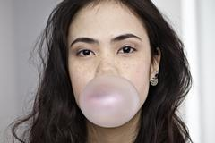 Germany, Cologne, Young woman blowing bubble gum Stock Photos