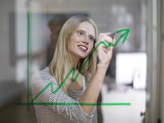 Germany, Cologne, Young woman drawing graph on glass Stock Photos