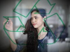 Stock Photo of Germany, Cologne, Young woman drawing recycling symbol on glass