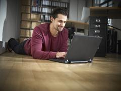 Stock Photo of Germany, Cologne, Mid adult man using laptop