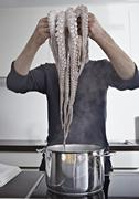 Germany, Cologne, Mid adult man cooking octopus in kitchen Stock Photos
