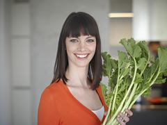 Stock Photo of Germany, Cologne, Mid adult woman holding vegetable, smiling, portrait