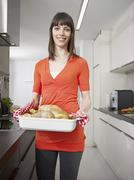Germany, Cologne, Mid adult woman with roasted chicken, smiling, portrait Stock Photos