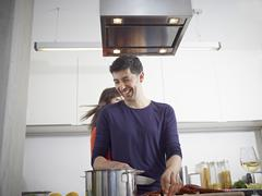 Germany, Cologne, Man and woman cooking together in kitchen Stock Photos
