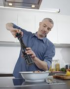 Germany, Cologne, Mature man cooking food in kitchen Stock Photos