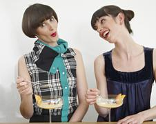 Germany, Cologne, Women eating dessert in kitchen Stock Photos