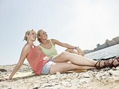 Germany, Cologne, Young women sitting on riverbank Stock Photos