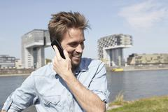 Stock Photo of Germany, Cologne, Mid adult man talking on cell phone