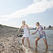 Stock Photo of Germany, Cologne, Young women skipping stones in river