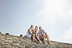 Germany, Cologne, Young women sitting on rivernbank - stock photo